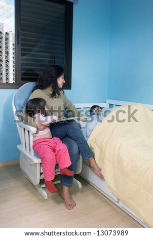 Mother reading a story to her children at bedtime - stock photo