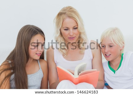 Mother reading a story to her happy children