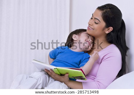 Mother reading a story to her son - stock photo