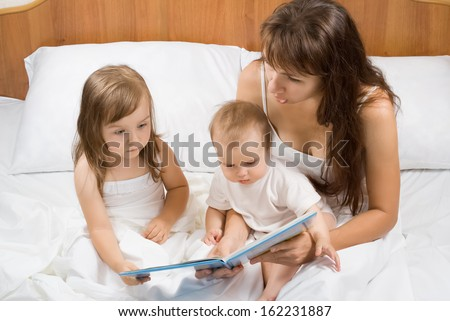 Mother reading bed time story book to children in bed