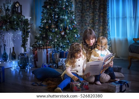 Mother reading book her daughters at Christmas Eve
