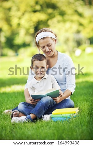 Mother reading book in the park - stock photo