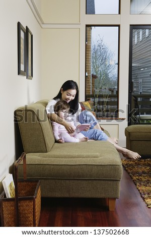 Mother reading book to daughter - stock photo