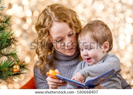 mother reading book to kid at Christmas tree