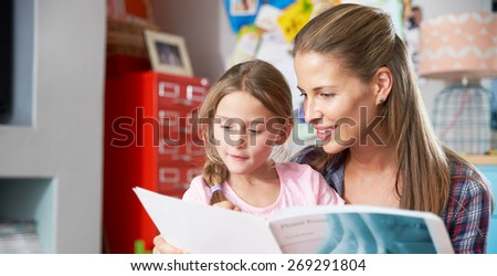 Mother Reading Book With Daughter In Bedroom - stock photo