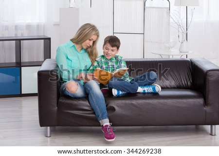 mother reading his son a children's book in a light room - stock photo