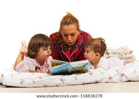 Mother reading story to her kids in bed before sleep - stock photo