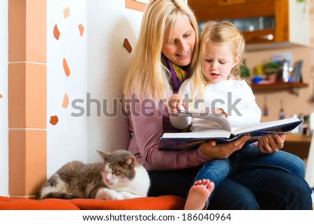 Mother reading tired daughter good night story out of storytelling book - stock photo