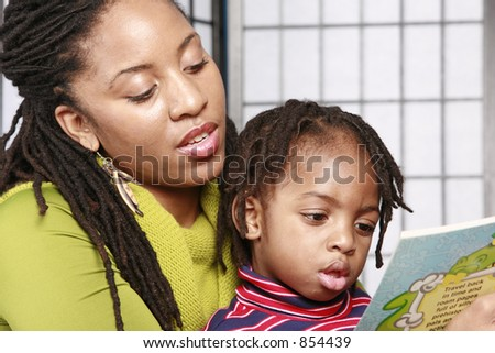 Mother reading to her son - stock photo