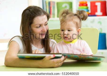Mother reading with her child daughter at table