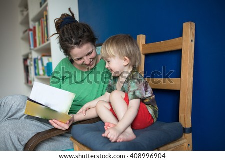 Mother reading with her son at home, casual, real interior, blue wall, lifestyle - stock photo
