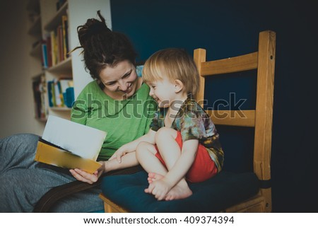 Mother reading with her son at home, casual, real interior, blue wall, lifestyle, toning - stock photo