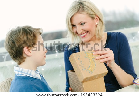 Mother receiving a christmas gift from her son - stock photo