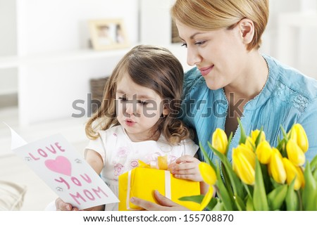 Mother receiving bunch of flowers from her daughter - stock photo