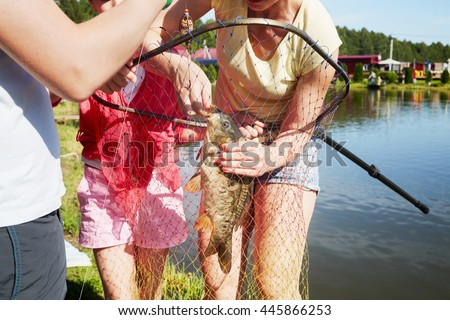 Mother removes a hook from a mouth of the caught carp at pond bank, two children stand near.