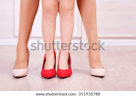 Mother's and daughter's legs in shoes