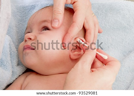 Mother's clean hands are cleaning her baby after the bath.
