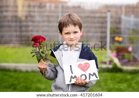 Mother's Day - Boy giving his mother self-made greeting card and flowers - red roses. - stock photo