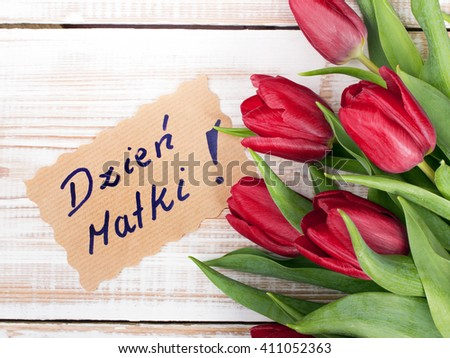 "Mother's Day card and a bouquet of beautiful tulips on wooden background, with Polish words ""Mother's Day"""