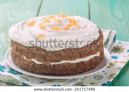 Mother's day carrot cake, homemade moist and sweet layer cake with grated carrot,  walnuts and dried apricot topped with swirls cream cheese frosting.  Delicious delight for holiday. Pastel tones - stock photo