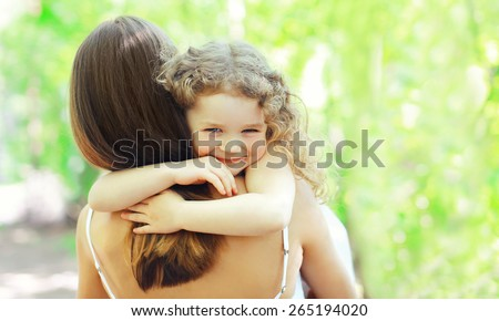 Mother's day, family, childhood and people concept - happy daughter hugging mother in warm sunny summer day on the nature - stock photo
