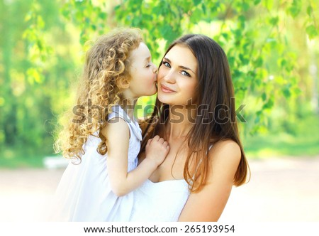 Mother's day, family, childhood and people concept - loving daughter kissing mother, happy young mom and child in warm sunny summer day on the nature - stock photo