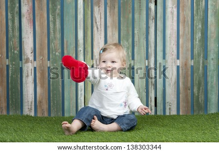 Mother's day : little baby with small red heart pillow, seated on grass - stock photo