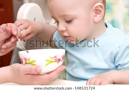 Mother's hand feeding baby boy - stock photo