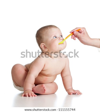 Mother's hand feeding baby with a spoon