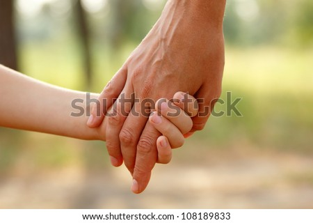 mother's hand lead her child son in summer forest nature outdoor, trust family concept