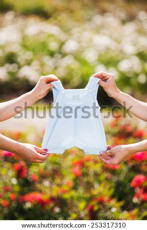 Mother's hands holding a baby's clothes. outdoor - stock photo