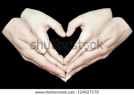 Mother's hands holding child's hands making heart sign - stock photo