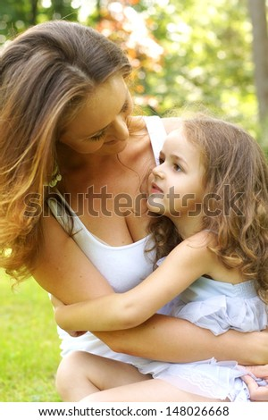 mother's love. daughter sitting at mothers knees - stock photo