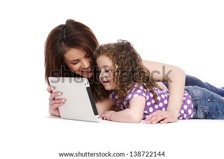 Mother sat with a little girl on her knee playing on a computer tablet isolated on a white background - stock photo