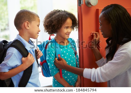 Mother Saying Goodbye To Children As They Leave For School - stock photo