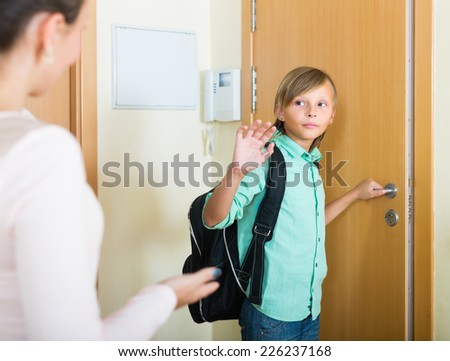 Mother saying goodbye to her schoolboy son at doorway  - stock photo