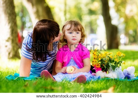 mother says something to her daughter's ear. summer park - stock photo