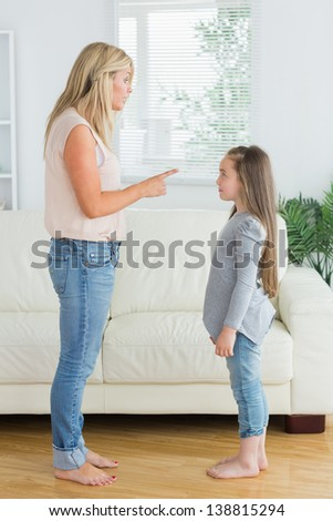 Mother scolding daughter in the living room - stock photo