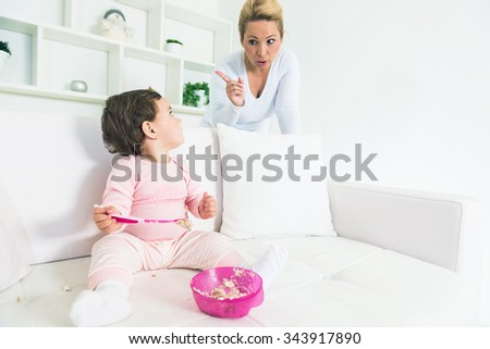 Mother scolding her little baby girl while she eating a cake on  sofa and pieces of cake falling down all around.Copy space, shallow doff - stock photo