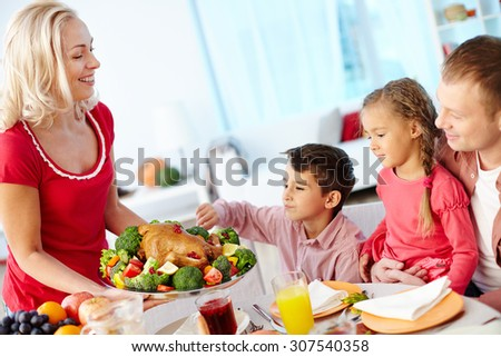 Mother serving chicken for dinner - stock photo