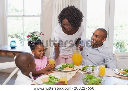 Mother serving juice to her family at lunch at home in the kitchen - stock photo