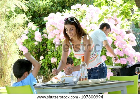 Mother serving lunch to kids in home garden - stock photo