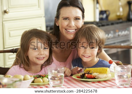 Mother Serving Meal To Children In Kitchen - stock photo
