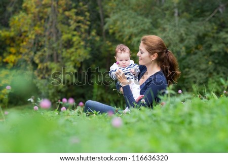 Mother showing her baby a clover flower on a beautiful summer day - stock photo