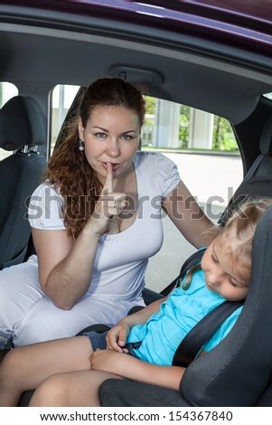 Mother showing shh gesture when daughter asleep in car safety seat - stock photo