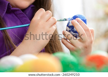 Mother showing to her children how to paint  Easter eggs