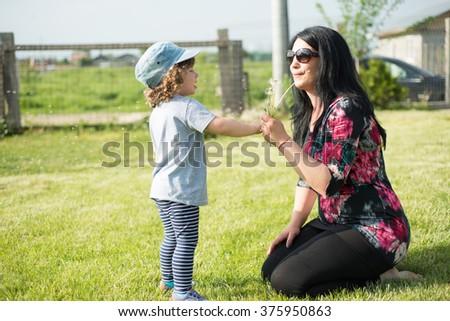 Mother showing to her toddler how to blowing dandelion