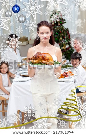 Mother showing turkey for Christmas dinner against snow falling - stock photo