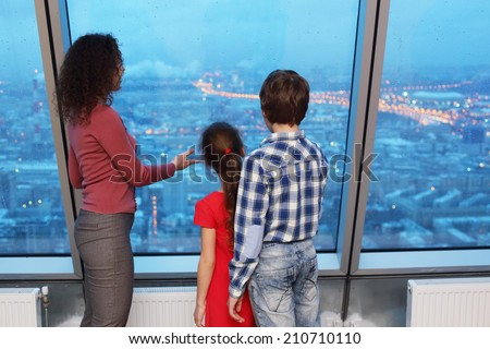 Mother shows children evening cityscape by a large window - stock photo