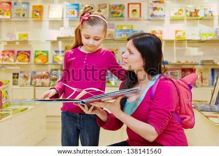 Mother shows to daughter big fold-out book in book department of store - stock photo